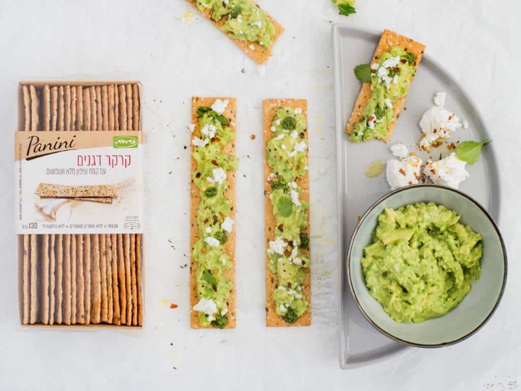 חברת כרמית חולקת מתכון קרקר דגנים עם אבוקדו פסטו ארוגולה וגבינת עזים צילום גלי איתן.